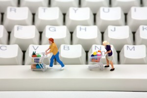 Miniature shoppers with shopping carts on a computer keyboard. Online shopping concept.